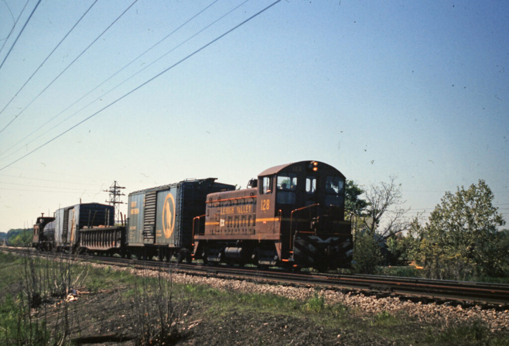 LV Rochester Local 1.5 miles east of Mendon w/#128 SW900m leading. 5/22/1973. Collection of Charles Woolever.