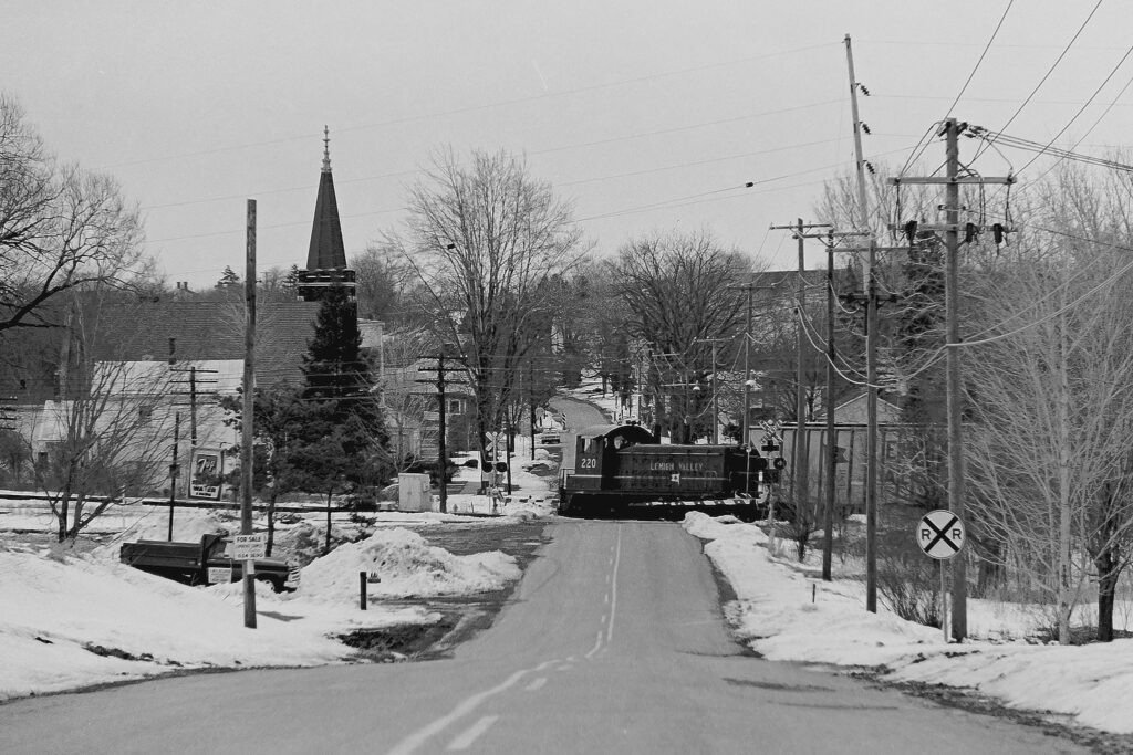 Eastbound Lehigh Valley RR local RM-2 crossing NY Rt. 251 Mendon, NY March 19, 1974. The foundation for the crossing signal on the right can still be seen in the ground, with the bolts bent over along Route 251. Mendon station park is to the right now. Paul J. Templeton photo.