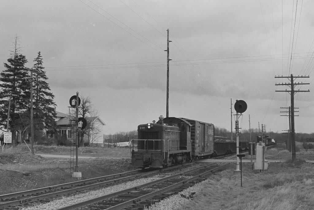 Lehigh Valley Railroad local MR-1 crossing Mile Square Road east of Mendon, NY on April 12, 1973. Train is Westbound. Signal on the left is now located in the Lehigh Valley Veterans park in Manchester, Relay case to the right of the right signal (#3732) is still there. Paul J. Templeton photo.