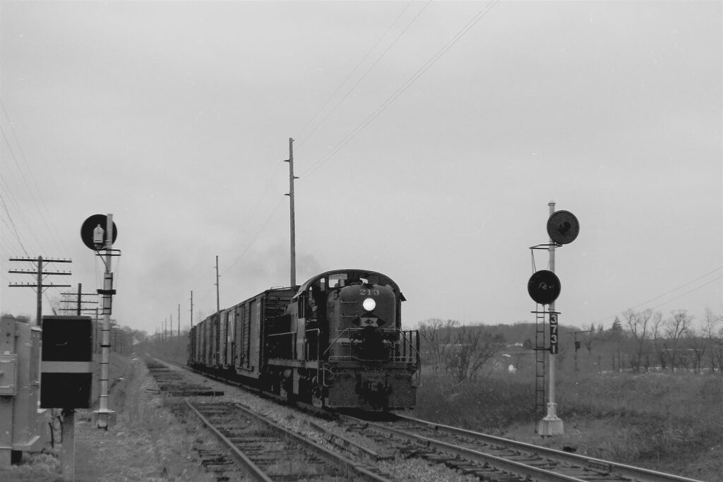 Eastbound Lehigh Valley RR local RM-2 at Mile Square Road in Mendon, NY, late February 1976. The Hamlet of Mendon is behind the train about 3/4ths of a mile. Signal 3731 is now at the Lehigh Valley Veterans Memorial Park in Manchester NY as a tribute to Engineer Jack W Parmele. Roughly a month after this photo was taken, The Lehigh Lehigh Valley Railroad would shut down forever and faded into history. The R.O.W. is now known as the Lehigh Valley Trail. Paul J. Templeton photo.