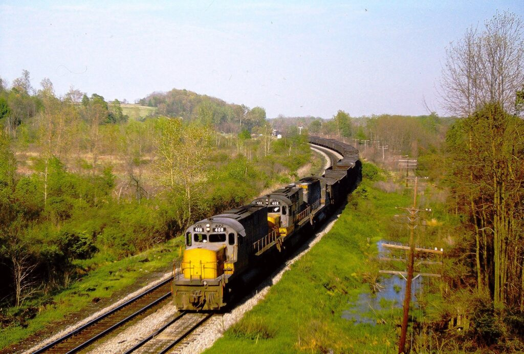 """Lehigh Valley VRR train BNW-3, with 3 Alco C420 """"Yellowjackets"""" heading west on May 21, 1974. This photo was taken from the Route 65 (Clover Street) bridge, which was about a mile east of Rochester Junction. If you look closely, you can see the interlocking signals, all red, at Quaker interlocking, which is by the curve. Paul J Templeton photo."""