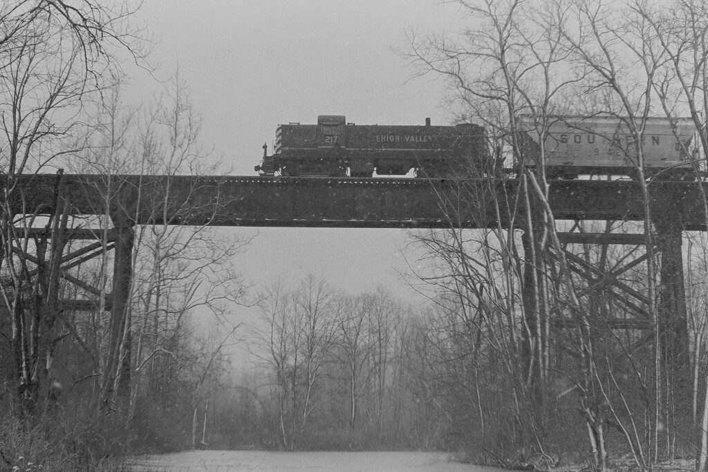 """Lehigh Valley RM-2 crossing Honeoye Creek on the """"Pa-Pa"""" Trestle, just outside of Honeoye Falls, March 26, 1975. These were Rochester branch tracks that came off the mainline tracks at Rochester Junction. Bridge was torn down in 1986. Paul J. Templeton photo."""