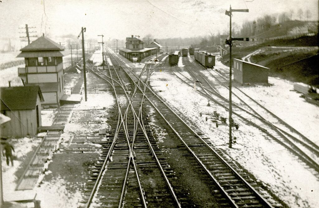 Lehigh Valley Rochester Junction, Honeoye Falls NY, early 1900s. View is railroad West. Crossover track in the center of the photo was the Rochester Branch, and went to the City of Rochester in one direction and to Honeoye Falls, Lima, and Hemlock in the other. Honeoye Falls - Town of Mendon Historical Society Collection.