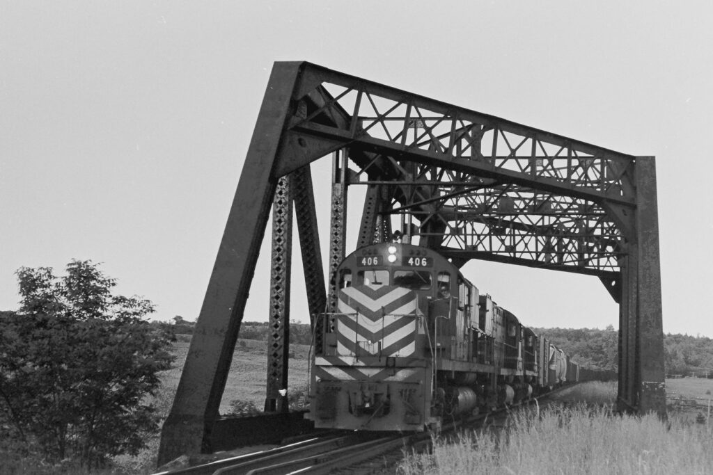 Westbound Lehigh Valley freight crossing bridge over the NYC Auburn branch, and about to cross Phillips Rd, taken on 10 June 1975. Now part of the Lehigh Valley Trail. Paul J. Templeton Photo.