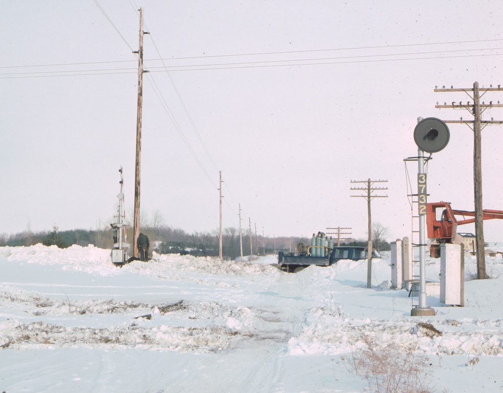 Removing the crossing signals at Mile Square Road in Mendon, NY on the Lehigh Valley Railroad. View is east. Tracks were gone summer of 1977, this picture was taken in Feb, 1978. This is now part of the Lehigh Valley Trail. Paul J. Templeton photo.