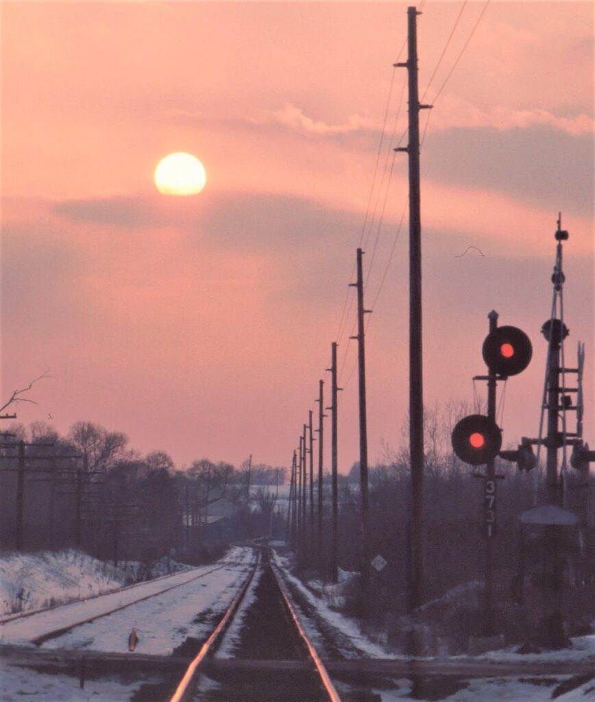 Lehigh Valley Railroad westbound looking to Mendon NY. Mile Square Road grade crossing. Old main track no. 2 is out of service by this time. Late afternoon, February 23, 1973. Double head signal #3731 was the approach signal for Quaker interlocking. Paul J. Templeton photo.