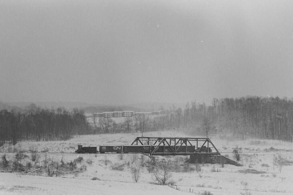 Lehigh Valley RR local RM-2 crossing the bridge over the former NYC Auburn branch near Phillips road in Victor NY. This bridge still stands. A cold February 8, 1973. Now part of the Lehigh Valley Trail. Paul J. Templeton photo.