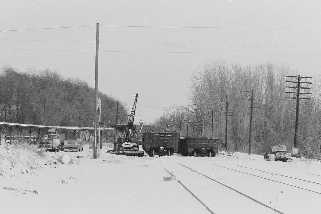 A&K Track Materials gang loading rail into gondola cars at ex Lehigh Valley Rochester Jct. January 16, 1978. Rumor going around at the time related that A&K let a loaded gon get away and it rolled towards Rush, finally stopping. The A&K Pettibone could not pull the car so the crew of Conrail EX-1 was talked into going down the abandoned track in order to pick the car up and drag it back to RJ. Never had confirmation of that story, however. Only the Lehigh Valley mainline tracks east and west of Rochester Junction were removed. The Junction itself was still being accessed by Conrail via the Rochester branch for deliveries to Honeoye Falls and Lima until the early 1980s, when everything else was ripped up. Paul J. Templeton photo.