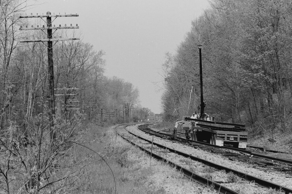 A&K Track Materials picking up rail just east of ex Lehigh Valley Railroad Rochester Jct. on May 21, 1978. That gal handing the rail was the truck driver's girlfriend. You can see the 3 track bridge over Honeoye Creek, which still stands, in the background. Paul J. Templeton photo.