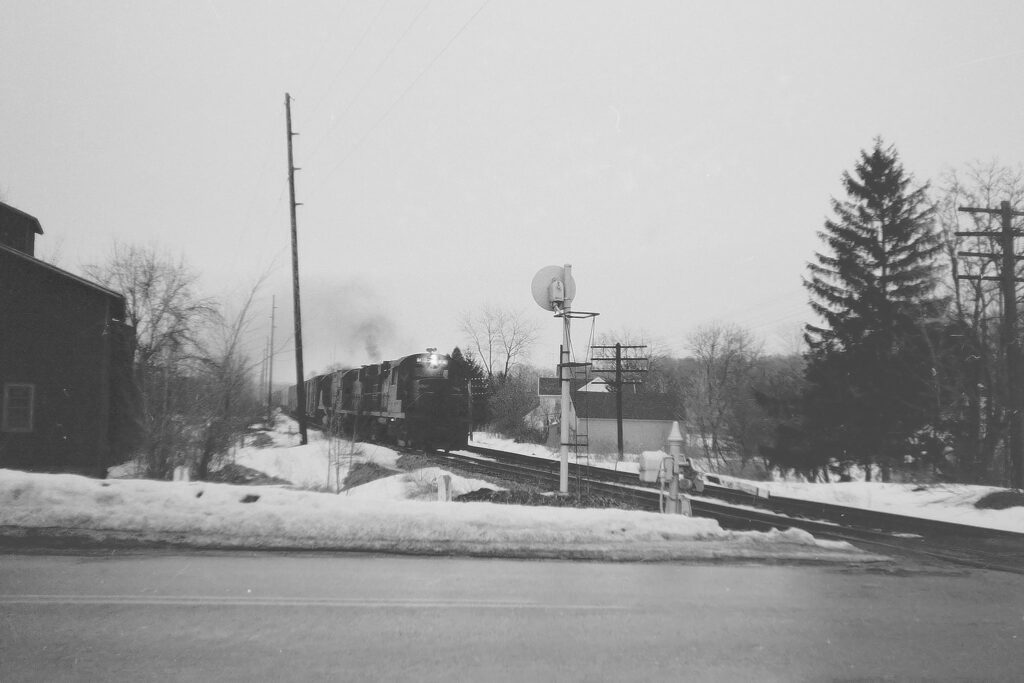 Lehigh Valley freight about to cross Route 64 in Mendon NY, Winter 1971. Still rule 251, Automatic Block System. In two years, mainline track no. 2 would be out of service. Paul J. Templeton photo.