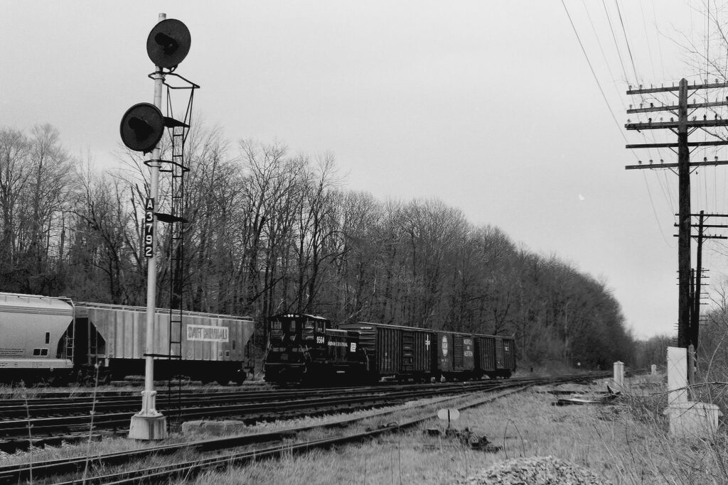 Conrail local EX-1 working at ex Lehigh Valley Railroad Rochester Jct. April 6, 1976. Signal 3792, which was the approach signal for Quaker interlocking, was still lit but was set at Red Over Red and stayed lit that way until Conrail disconnected the power. Did not matter as the mainline was no longer being used, just the Rochester Branch. Cars were going to concerns in Honeoye Falls and Lima. Paul J. Templeton photo.