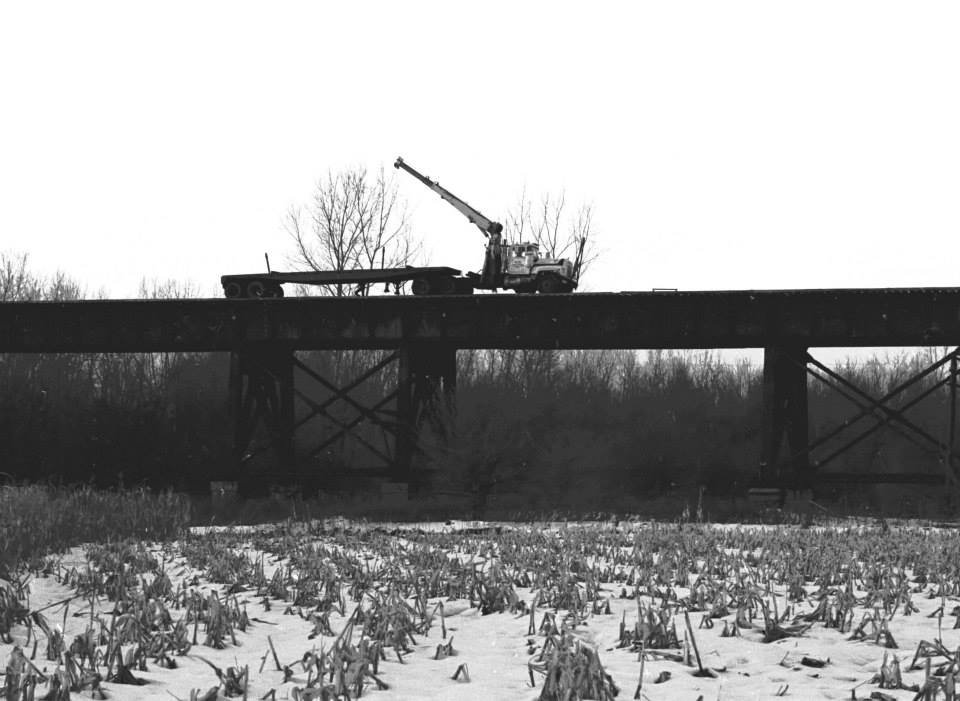 Here is a photo that depicts A&K pulling rail from the trestle that led up to the bridge that went over the Erie Railroad, Genesee River, and Pennsylvania Railroad on the Lehigh Valley mainline. The bridge still stands and is part of the Lehigh Valley Trail. The tracks went on top of the bridge, not through it like it is now. The approach trestles are gone. Taken from the south side on the very late afternoon of a chilly 16 December 1977. Paul J. Templeton photo.