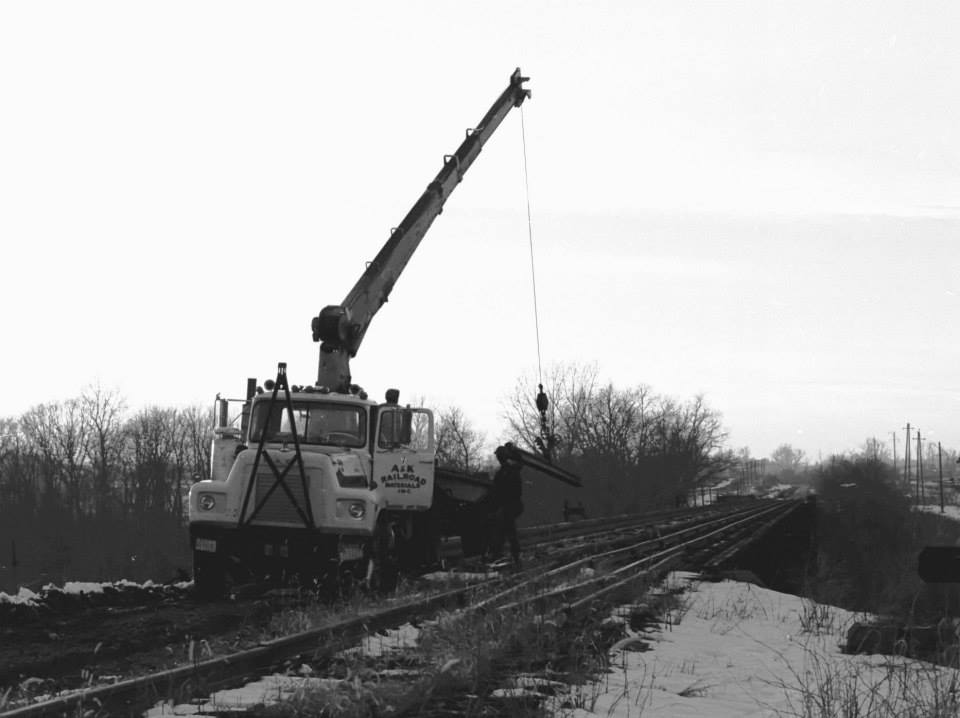 Another picture that depicts A&K pulling rail from the rail from the Lehigh Valley Genesee River bridge. Guardrails still in place. April 1977. Paul J. Templeton photo.