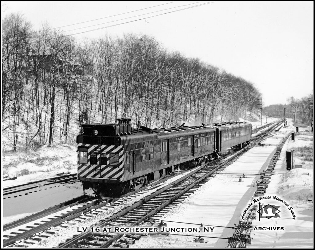 Lehigh Valley passenger train coming off the Rochester Branch from Hemlock and arriving at Rochester Jct., sometime in the 1930s. This view looks east from inside the interlocking tower, with the station behind the photographer. The branch to Rochester also connected here. This self-propelled gas-electric motorcar is towing an unpowered coach trailer, common for branch lines without a lot of traffic. The last regular Rochester Branch passenger service to Lima was discontinued on August 9, 1937. Photographer and date unknown. Anthracite Railroads Historical Society Collection.
