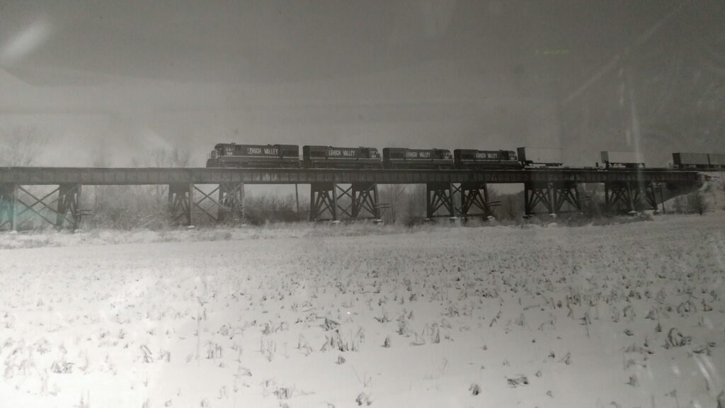 March 15, 1975 the Pride of the Fleet Apollo, Lehigh Valley AP-1 led by 4 USRA purchased GE U23Bs hustles across the Genesse River flood plain trestle that led up to the Genesee River bridge in the Town of Rush. David J. Monte Verde photo.