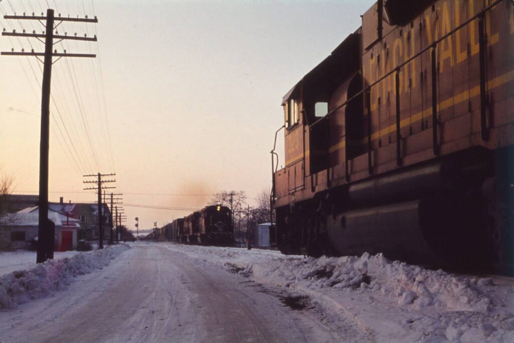 East-west meet at Rush interlocking, eastbound train heading for Rochester Junction waits for westbound train to clear the interlocking, two months before the end of the LV. The westbound train has just crossed route 15A. Christopher Smith photo.