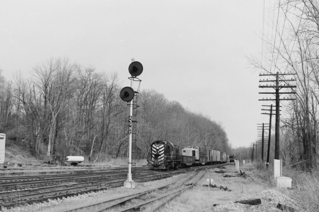 Lehigh Valley Railroad local MR-2 on scrap pickup train at Rochester Jct. The SP crane that had been picking up scrap broke down so it and the cars it was towing were picked up by MR-2. March 29, 1976, two days before the end of the Lehigh Valley. Paul J. Templeton photo.