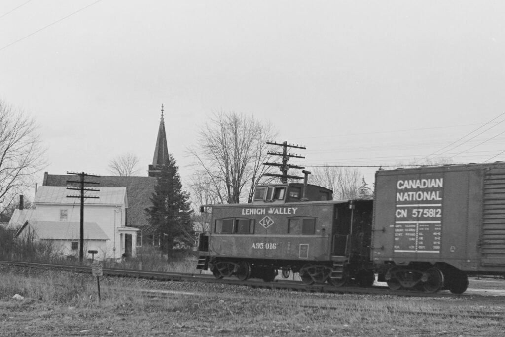 Lehigh Valley RR westbound train about to clear the NY Rt. 251 crossing in Mendon, NY on January 31, 1974. White house to the left of the Caboose is now Benincasa Hospice house. Paul J. Templeton photo.
