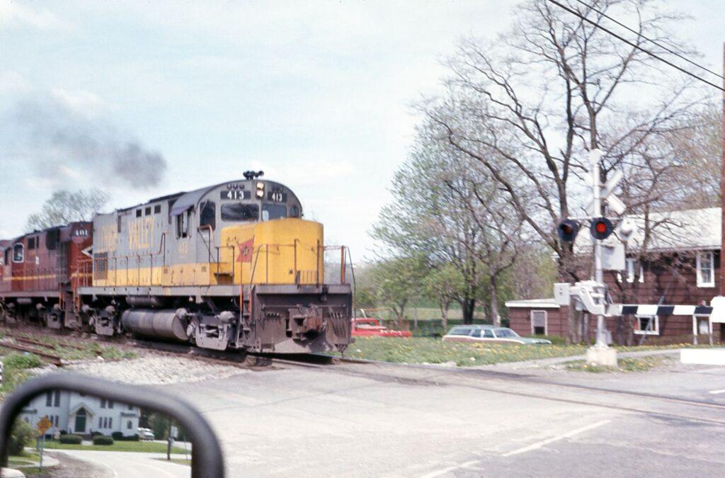 Gates down and a Lehigh Valley Railroad train rolls eastbound through Rush, NY, 1975. Ken Darron photo.