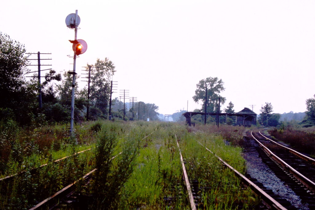 Shot of ex Lehigh Valley Railroad Rochester Junction on August 14, 1978. The sun was low in a hazy sky, so Paul Templeton lined it up with the empty signal. View is railroad west, and the tracks were gone on the other side of Plains Road by this time. Conrail was operating the Rochester branch at this time. Paul J. Templeton photo.
