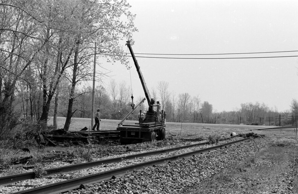 A&K Track Materials crew picking up Lehigh Valley Railroad rail near Clover Street. The overpass bridge has been removed and a newly paved Clover street is in its place. View is Eastbound and Rochester Junction is about a mile or so behind the photographer's back. May, 1978. Paul J. Templeton photo.