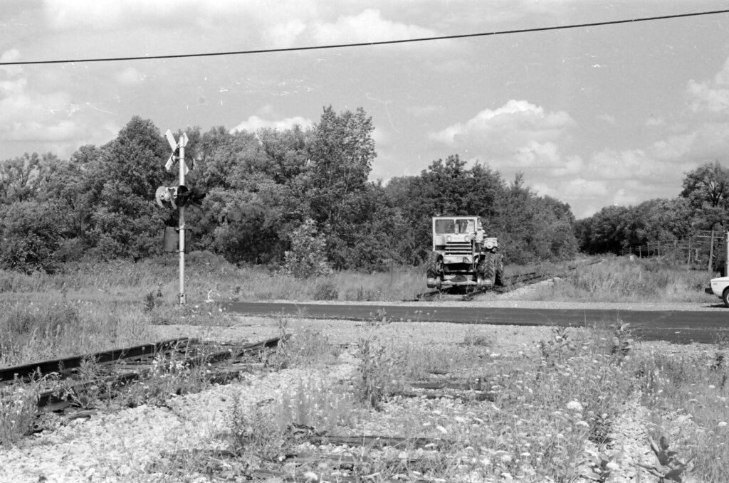 A&K Pettibone at the Lehigh Valley Railroad West Bloomfield road grade crossing in Mendon NY. Road has been repaved and rails removed on the road, signals still in place, MT 2 removed years earlier. The Hamlet of Mendon is a little over a mile beyond the curve. This is part of the Lehigh Valley Trail. August, 1977. Paul J. Templeton photo.