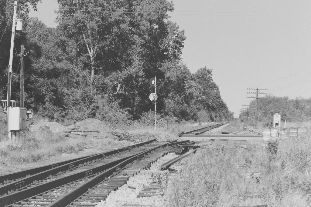 Lehigh Valley Railroad Quaker Interlocking, Quaker Meeting House Road, Mendon, NY, view to the east, June 21, 1977. Rail removed from the road and crossing signals removed. Paul J. Templeton photo.