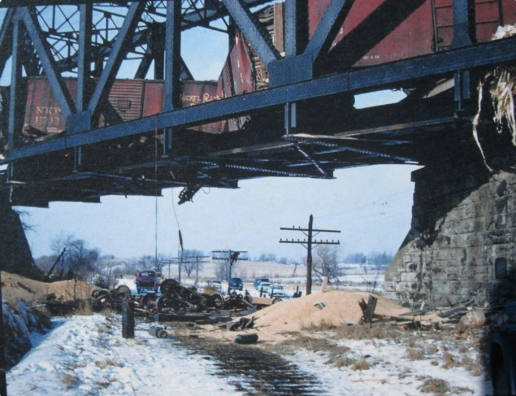 Lehigh Valley Wreck on Phillips Road bridge over the old NYC Auburn line. You can still see ties in the ground from the old Auburn line, which was just torn up prior to the LV derailment. Notice the man on the second telegraph pole.