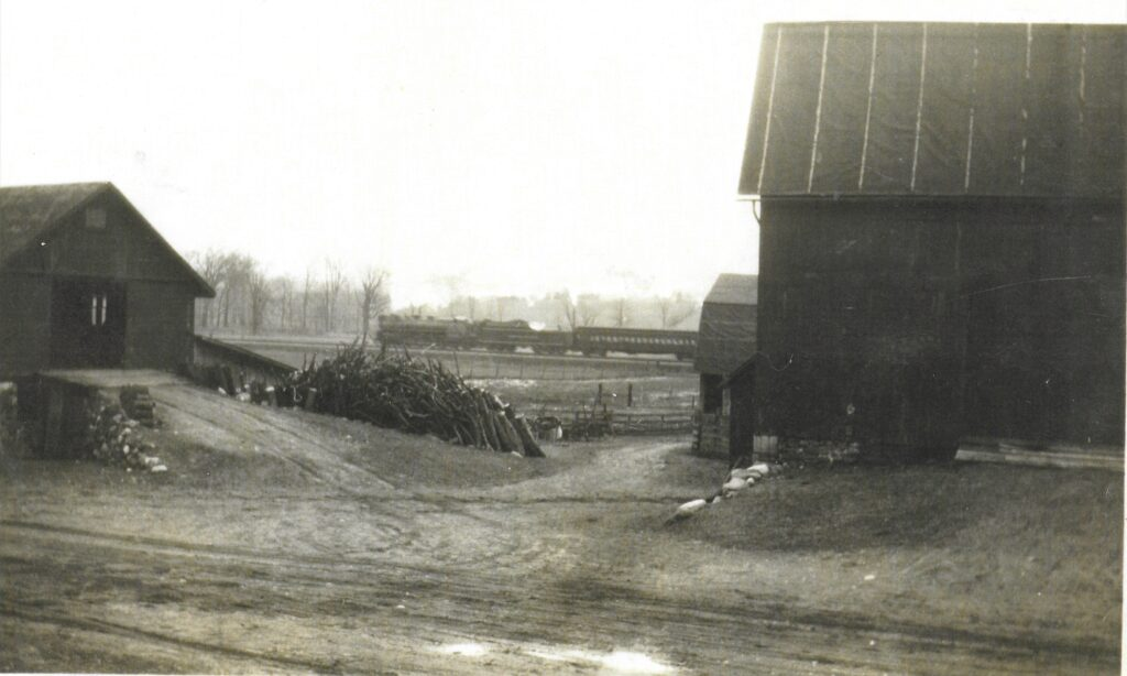 Willis and Ethyl Miller purchased the property at 287 Bull (Bulls) Saw Mill Road from John and Rebecca Bull. Included in the sale was the saw mill for which the road was named. This picture is looking south across Bull Saw Mill Road. In the background is a Lehigh Valley passenger train headed east towards Mendon. It is about to cross West Bloomfield Road. The path of the train is now the Lehigh Valley Trail. In the foreground there is a barn on the right. The building on the left is the saw mill, relocated from its original location. Honeoye Falls - Town of Mendon Historical Society Collection.